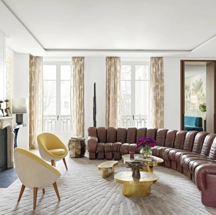 grande salón decorado en estilo vintage, muebles de diseño en amarillo y dorado, sofá de cuero color marrón y cortinas en beige