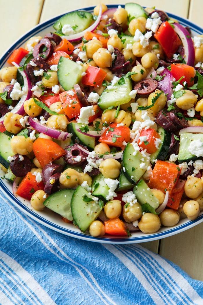 ensalada para los veganos, garbanzos cocidos con aceitunas negras, cebolla roja, queso blanco y tomates, ideas para comer sanas
