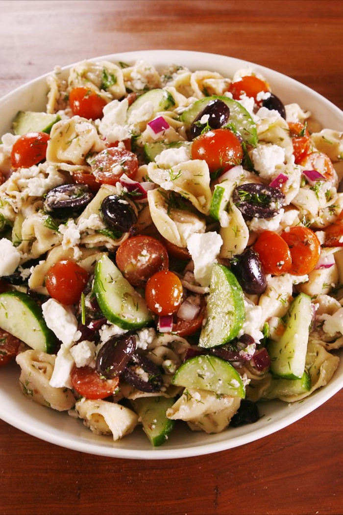 comidas faciles de hacer para una jornada en la oficina, ensalada con pasta, queso blanco, aceitunas, verduras y aderezo