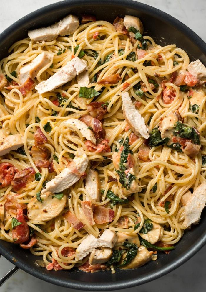 pasta en una sart'en con trozos de pollo, espinacas y tomates secados al sol, recetas sanas para cenar en bonitas fotos