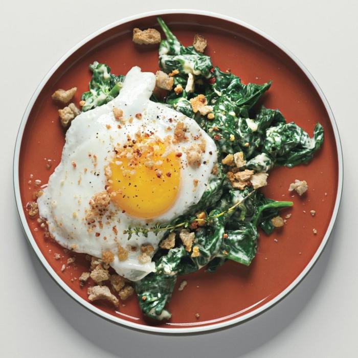 huevo estrellado sobre espinacas cocidas a la crema y nueces picados, comida sana recetas en bonitas imagenes
