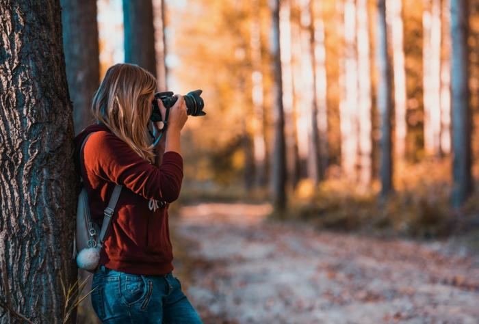 mujer tomando fotografias en un bosque en otoño, preciosos ejemplos de imagenes de reflexion que puedes contemplar para sentirte mejor
