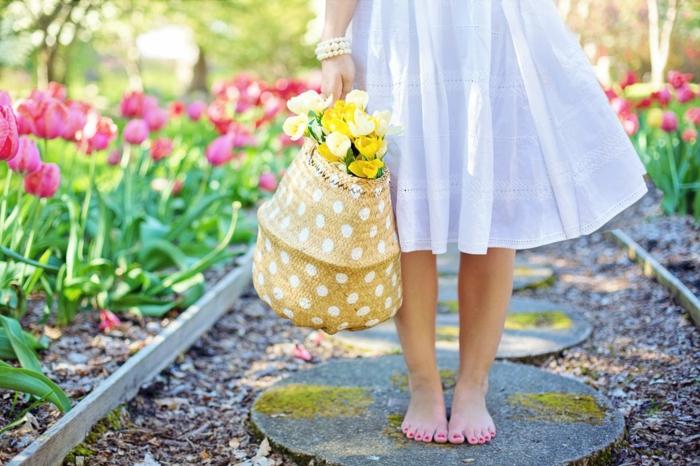 niña descalza con cesta de flores en primavera, paisajes bonitos del mundo, jardin con tulipanes grandes en color rojo