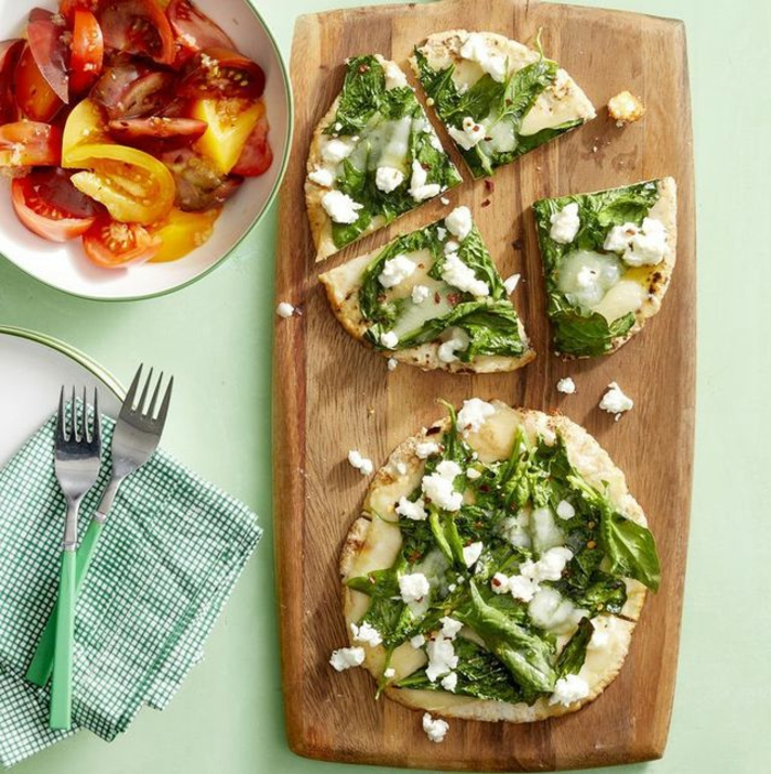 pizza de masa casera con hojas de espinacas frescas y queso blanco, ricas ideas de recetas para preparar en casa en primavera