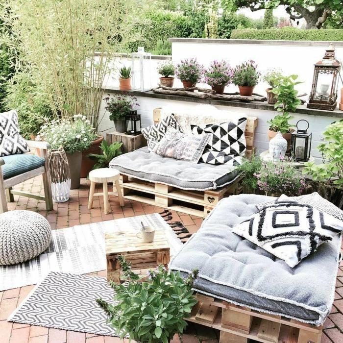terraza decorada en estilo mediterraneo con muchas platnas verdes, muebles de palets, silones de palets comodos y bonitos