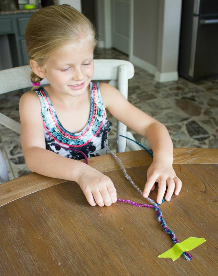 pequeña niña elaborando una corona de limpiapipas para regalar a su madre, ideas regalo dia de la madre, fotos de regalos DIY