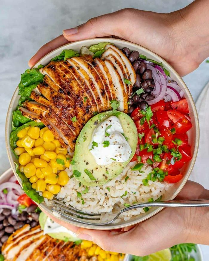 bol con arroz, maiz, pollo a la parilla, frijoles negros, cebolla roja, tomates y aguacate, que comer despues de entrenar ideas