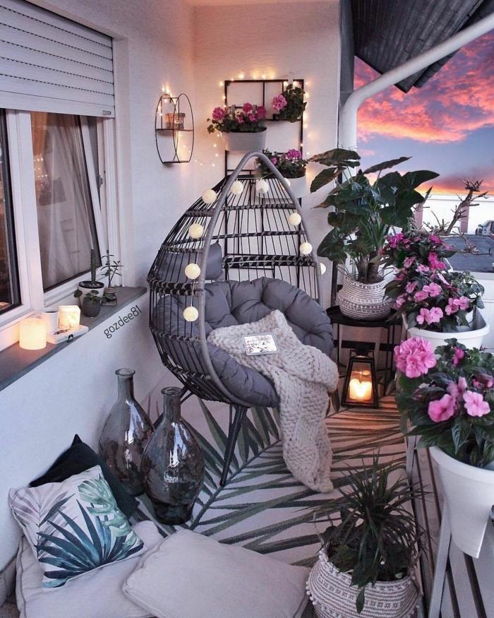 hermosa terraza con cojines, mantas y muchas flores, decorar la terraza con guirnaldas de luces, chill out palets en fotos