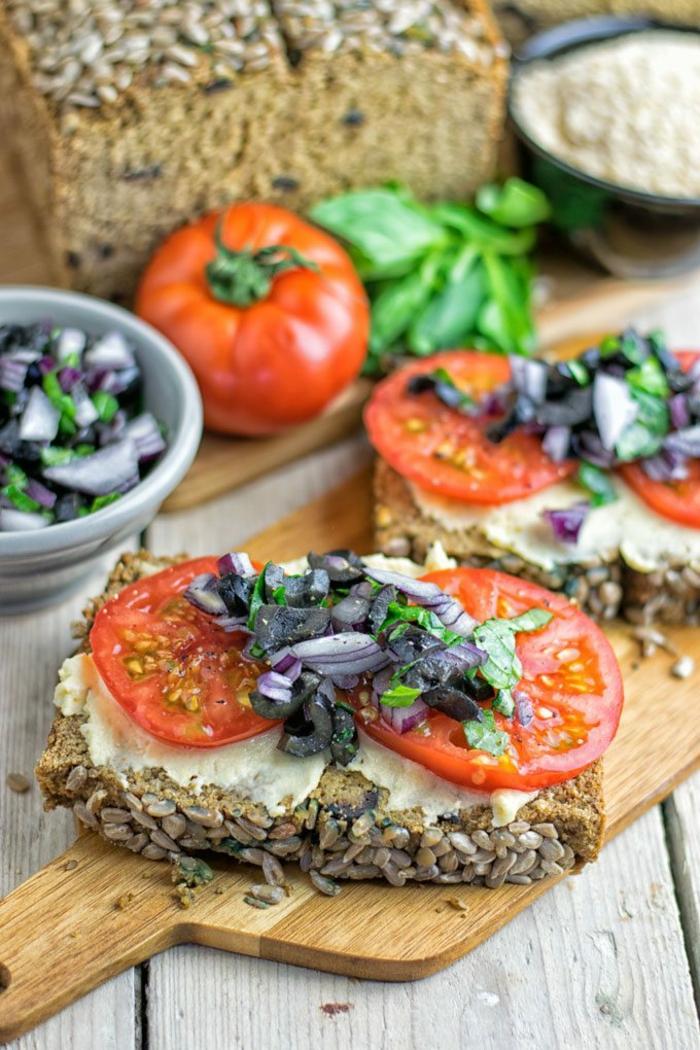 rebanadas de pan integral con semillas, hummus casero, tomates, cebolla roja y aceitunas negras, desayunos sanos