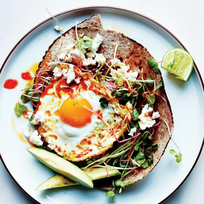recetas fitness en fotos, huevo estrellado en una tortilla integral, rebanadas de aguacate y lima, queso feta y verduras