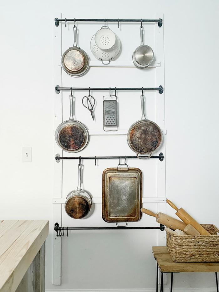 ideas sobre donde guardar las herramientas en la cocina, organizador colgante en la pared para las sartenes, ollas y bandejas