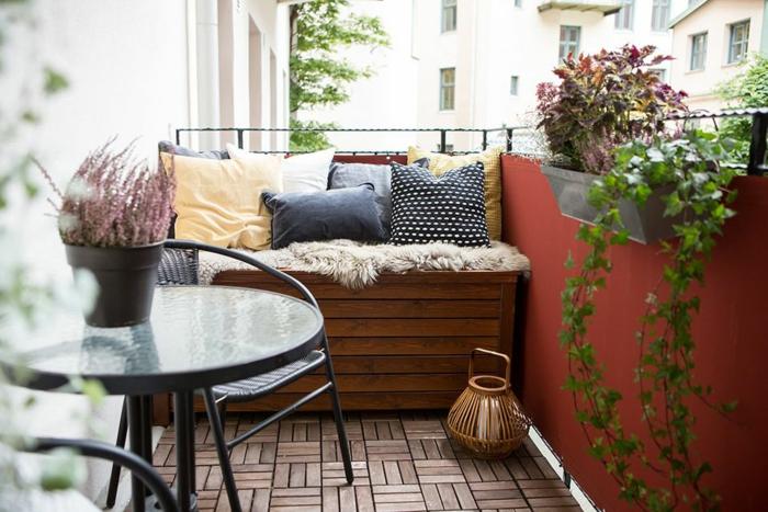 ideas super acogedoras sobre como decorar la terraza, mini sofa de madera, cojines deocrativos en diferentes colores