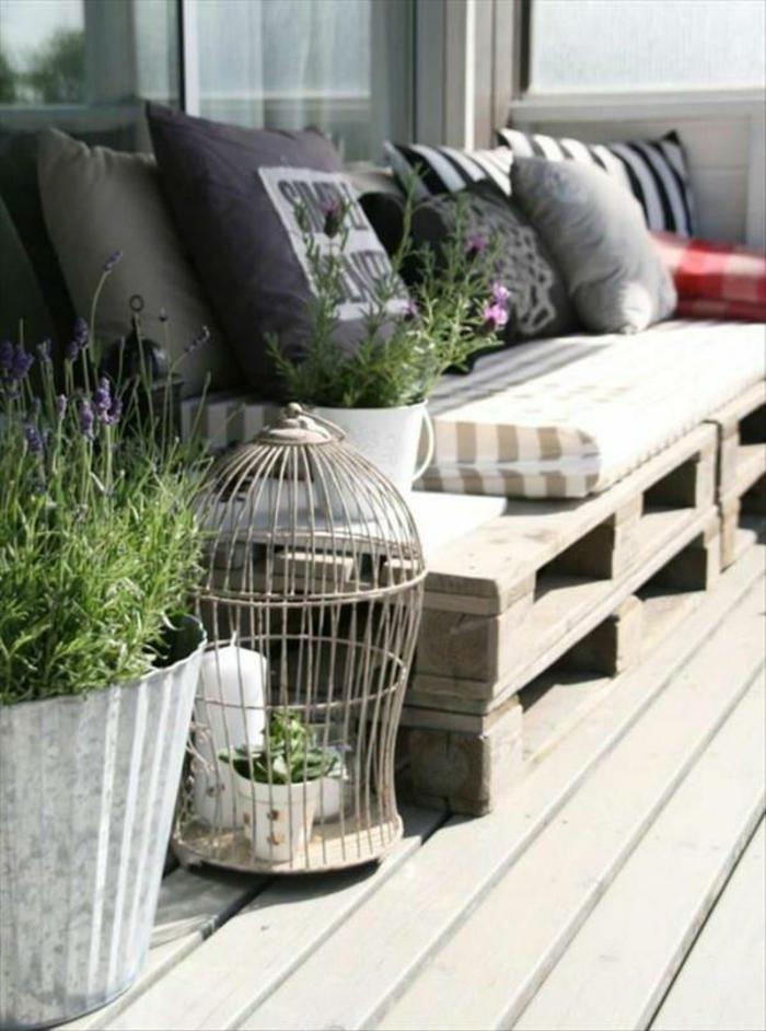 sofas hechos con palets decorados con cojines decorativos, macetas grandes con plantas verdes, ideas sobre como convertir la terraza en un espacio chill out