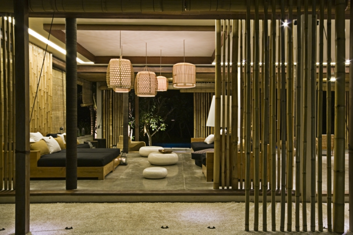 espacio decorado en tonos terrestres con muebles funcionales y modernos, separador de ambientes hecho de bambu