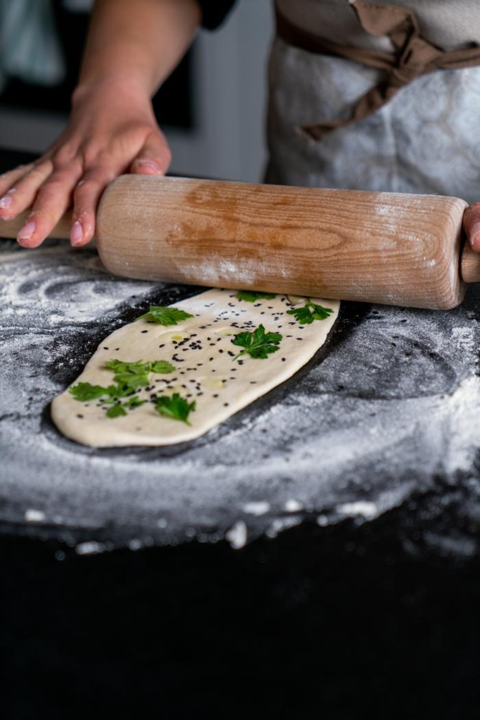 preparar pan indio tradicional paso a paso, estirar el pan añadiendo ajo, perejil, semillas de sesamo, receta de pan naan