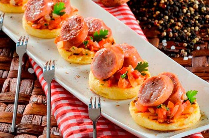 arepas con tomates picados,, cebolla y salchicas, originales ideas de entrantes para un picoteo con amigos en verano