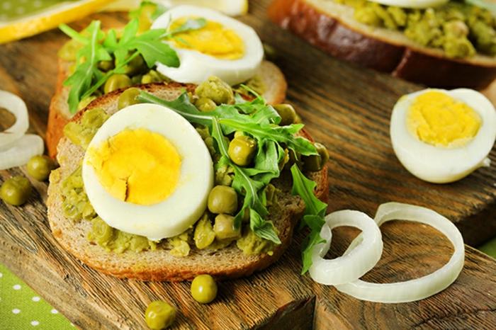 rebanadas de pan integral con guisantes hervidos, arugula fresca y huevos concidos adornados de cebolla, pinchos vascos