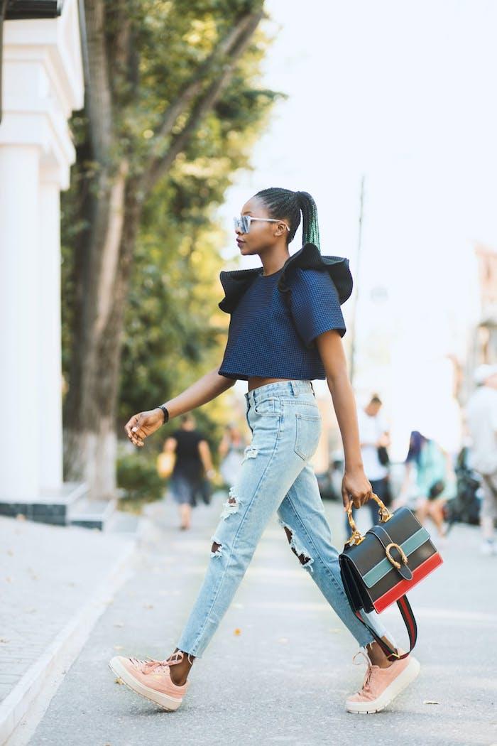 blusa azul mangas asimetricas grandes bolso moderno zapatillas color rosa vaqueros rotos