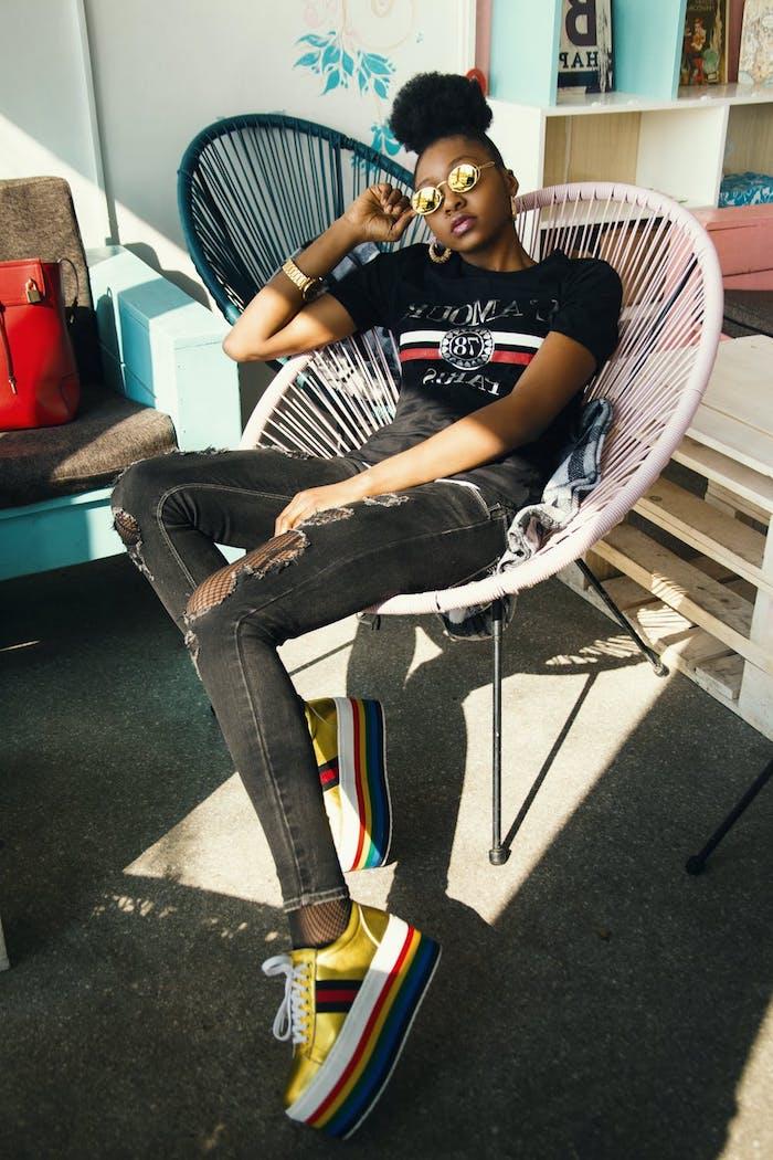 fotos tumblr en casa vaqueros negros rotos zapatillas altas dorado colores blusa negro pelo afro recogido en bollo gafas