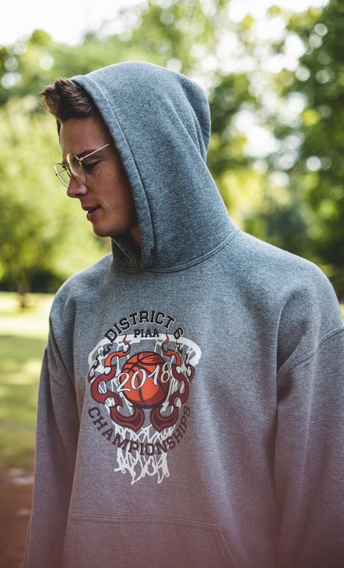 chico con sudadera gris gafas hipster estilo calle rizado corte de pelo hombre