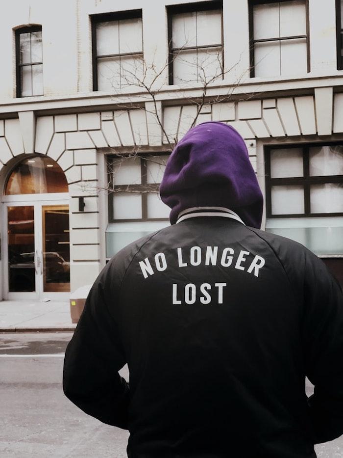 chico fotografiado en la espalda con sudadera negra con inscripción en la espalda street fashion