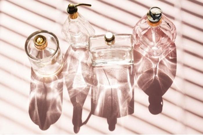 cómo elegir el mejor perfume perfumes en frascos transparentes sobre fondo rosa pálido