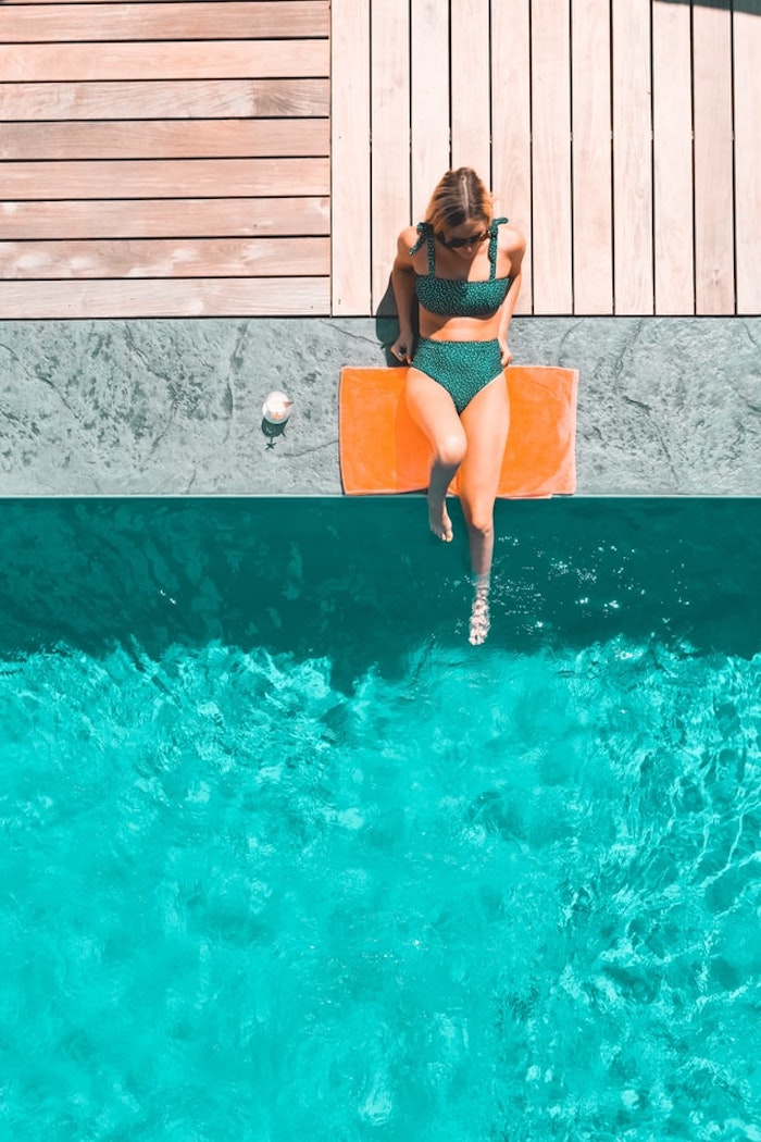 mujer junto a la piscina con bañador verde oscuro gran piscina al aire libre