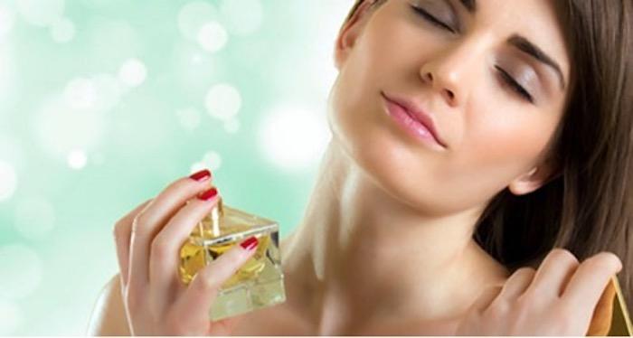 mujer que pone perfume en la puerta como elegir perfume para mujer