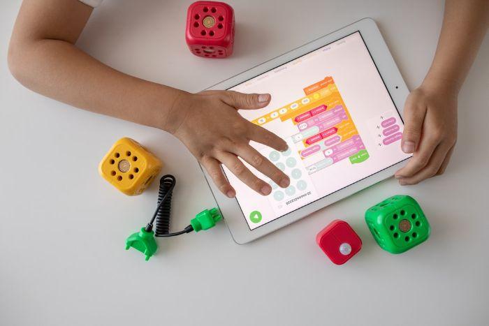 cubos verdes para juegos para niños tableta fondo blanco manos de un niño