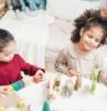 dos niños niñas que juegan con juguetes de madera en una sala de juegos