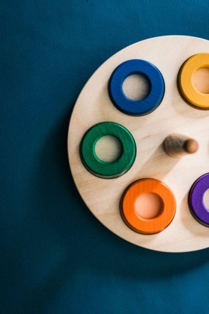 juguete de madera para niños con círculos de madera de colores sobre fondo azul