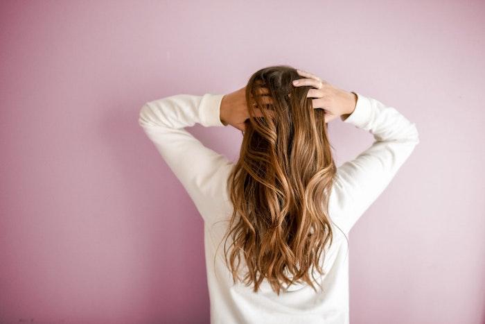 chica con cabello castaño claro sobre fondo rosa cuidado del cabello