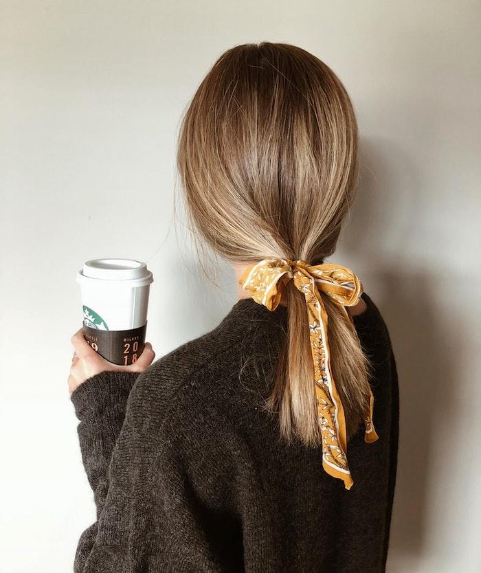 chica rubia oscura sosteniendo cafe starbucks hermosa banda de cabello amarillo
