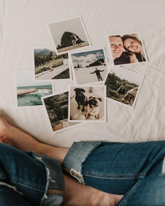 mujer con jeans azul sentada en una cama blanca fotos esparcidas en la cama