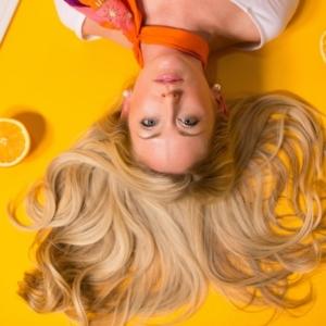 mujer joven con cabello rubio hombros largos acostada sobre un fondo naranja