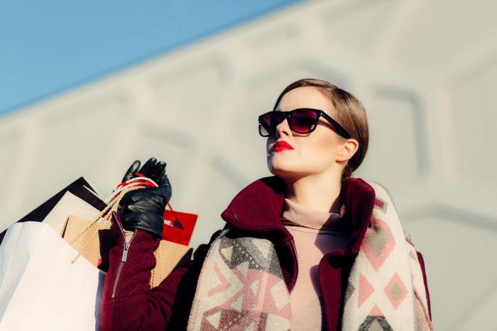 chica con gafas de sol pintalabios rojo y compras en mano.jfif