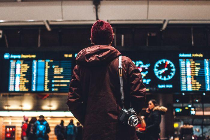 hombre en el aeropuerto fotografiado en la espalda con un sombrero tejido tableros electronicos en el aeropuerto.jfif