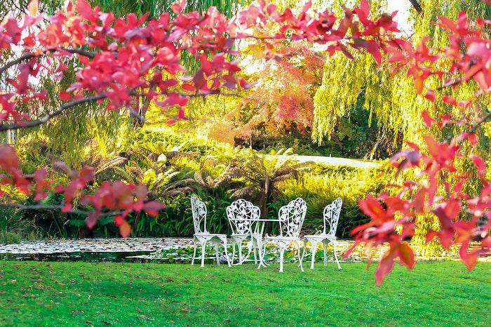 césped verde con sillas blancas y mesa de hierro forjado
