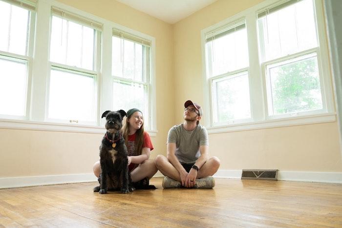 familia joven con un perro en una nueva casa bajo parquet