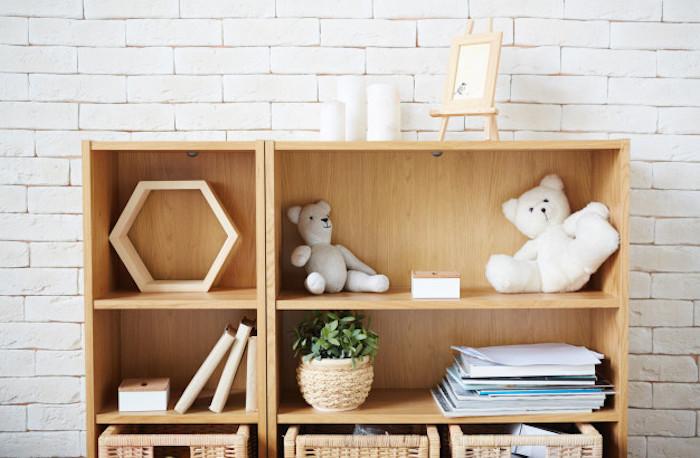gabinete de madera clara con estantes oso gris juguete