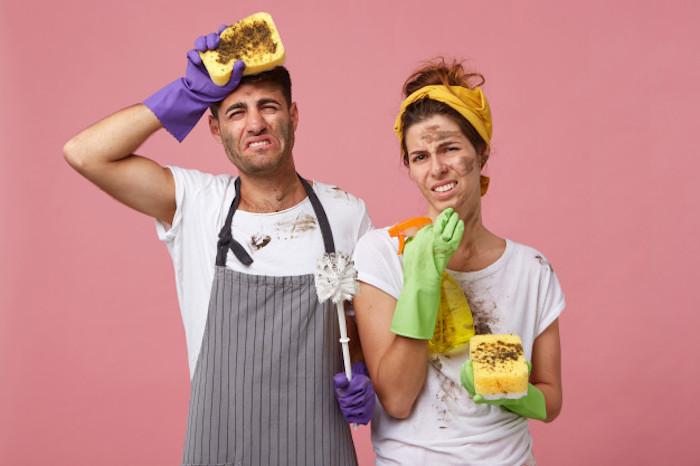 hombre y mujer pinta las paredes de la sala caras sucias