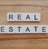 nombre scrabble para bienes raíces sobre fondo de madera