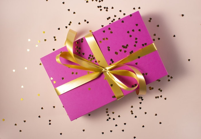 regalo en papel rosa con banda dorada