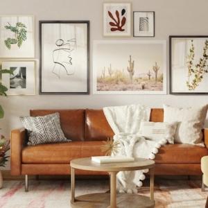 sofa de cuero con manta beige almohadas habitacion grande plantas verdes