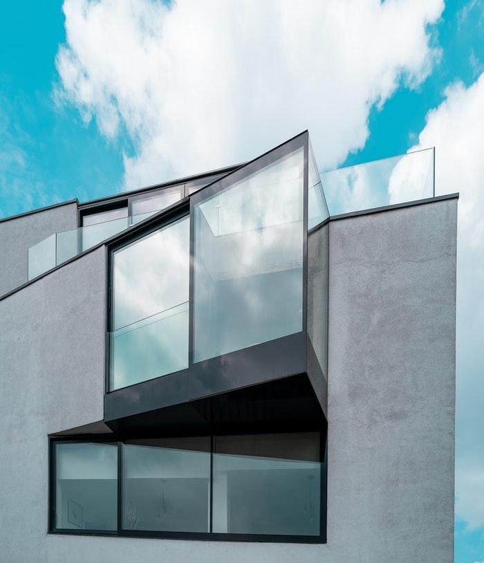 casa futurista construida con grandes ventanas y cemento