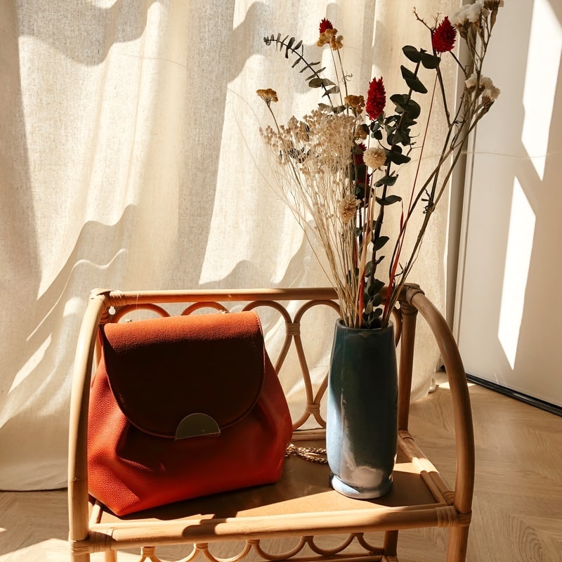 silla de madera clara mochila en color azulejo ramo de flores secas