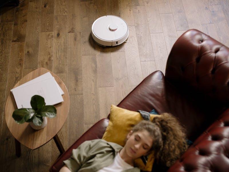 aspiradora robot niña acostada en un sofa de cuero