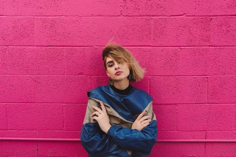 chica con peinado no estándar blusa azul fondo rosa