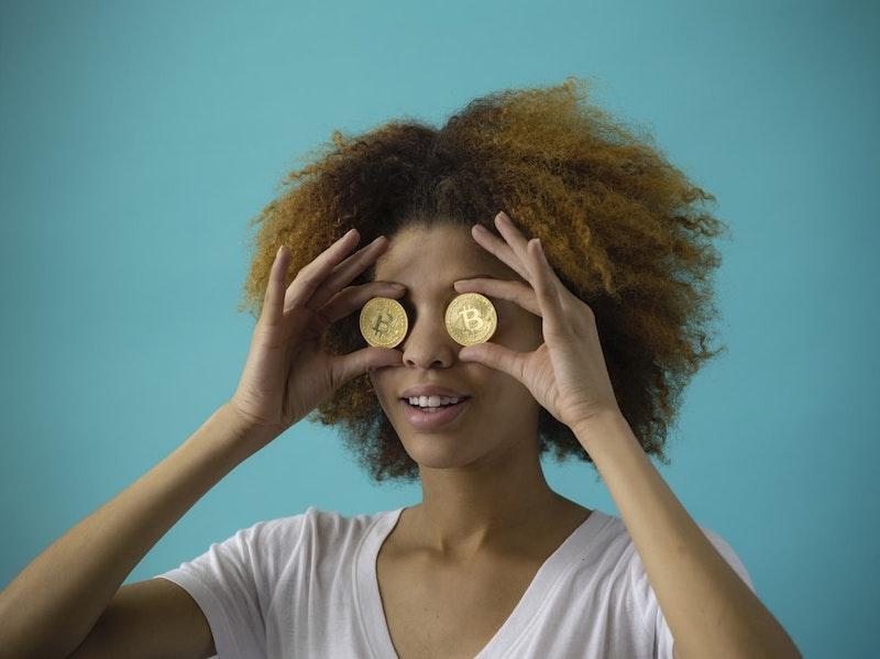 chica con pelo corto rizado con monedas colocadas ante los ojos