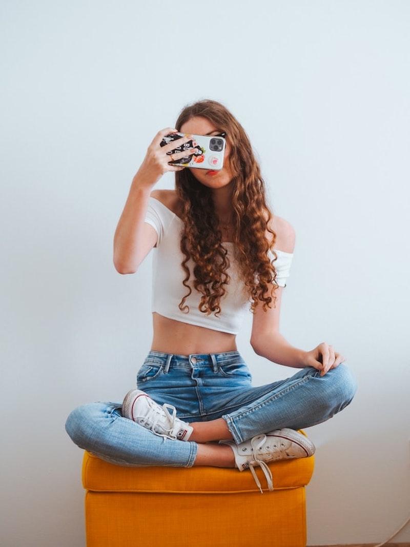 chica con pelo rizado jeans top blanco